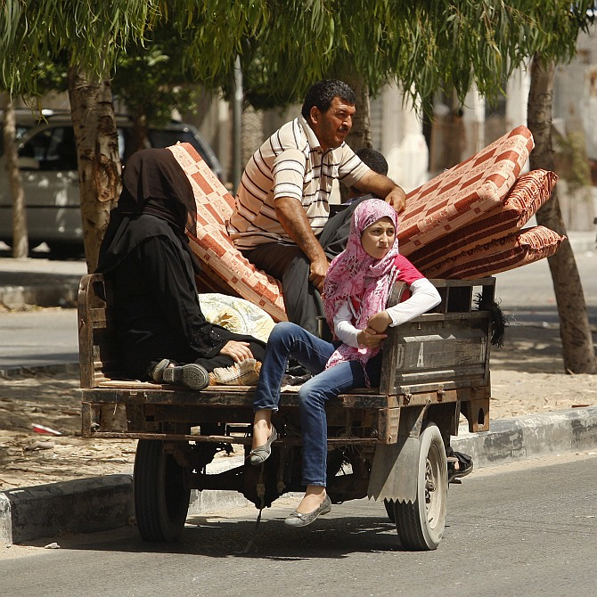 Palestinians, who fled their homes that are adjacent to the border with Israel, ride a motorised rickshaw as they make their way to stay at a United Nations-run school, in the northern Gaza Strip