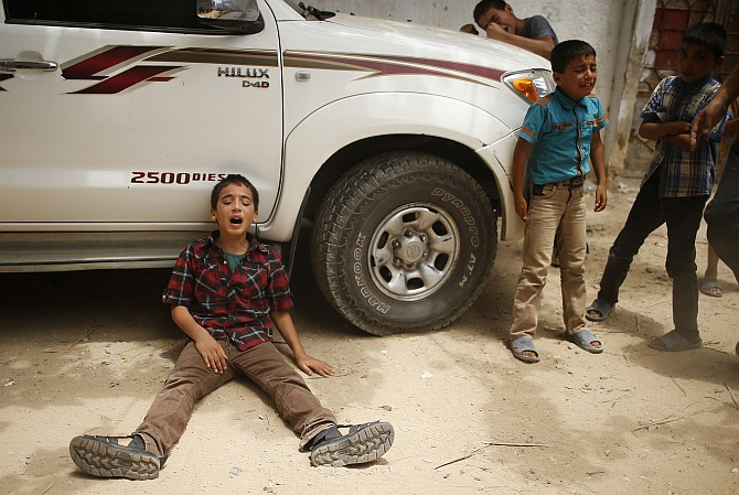 The son (left) of one of the Palestinian members of Tayseer Al-Batsh's family, who hospital officials said were killed in an Israeli air strike, mourns during their funeral in Gaza City. The Israeli air strike on the family home of Al-Batsh, Gaza's police chief, killed 18 people on Saturday, Gaza's health ministry said