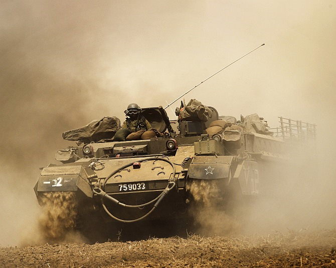 An Israeli armoured vehicle drives across a field near central Gaza Strip