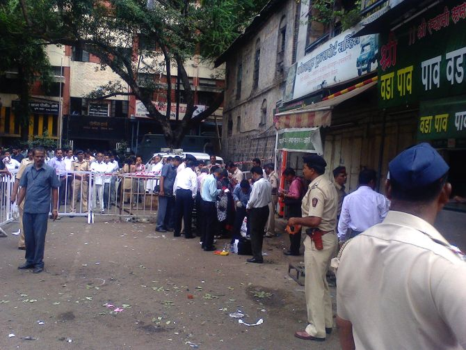 Officials inspect the site of the low-intensity blast in Pune, which injured five people.
