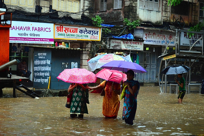 Women wade through knee-deep water near Dadar