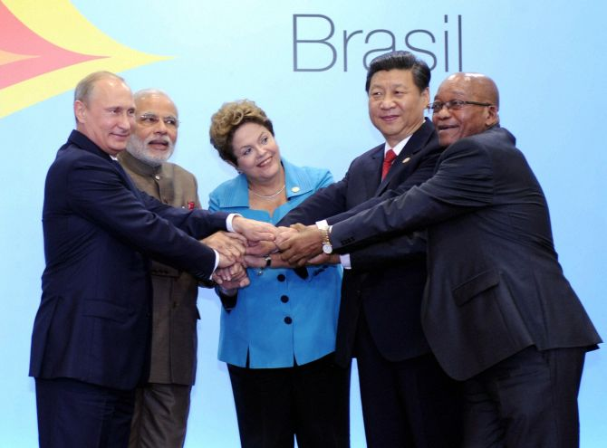 Prime Minister Narendra Modi join hands with Brazil's President, Dilma Rousseff, Russian President Vladimir Putin and Chinese President, Xi Jinping and South African President Jacob Zuma during the official photo of 6th BRICS summit.