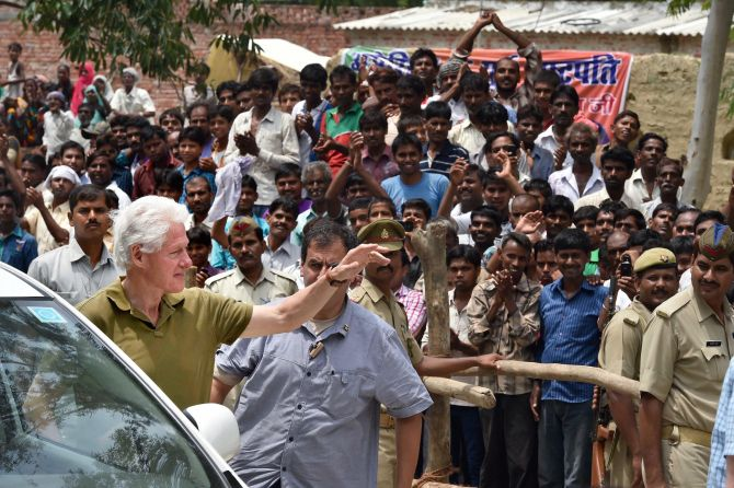 Former US President Bill Clinton waves upon his arrival at Mohanlal-Ganj in Lucknow district