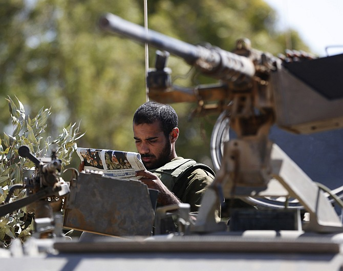 An Israeli Army reservist reads a newspaper as he sits atop an armoured personnel carrier (APC) outside the central Gaza Strip