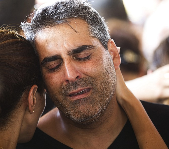 The brother of Dror Khenin mourns during his brother's funeral in Yehud, east of Tel Aviv, after Khenin was killed on Tuesday when a short-range rocket landed near the border with Gaza