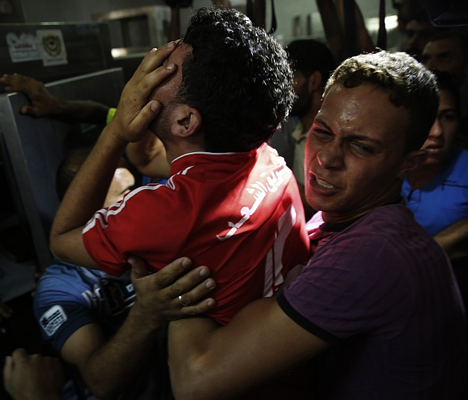A brother (C) of one of the four Palestinian children from the Baker family, whom medics said were killed by a shell fired by an Israeli naval gunboat, grieves inside the morgue in Gaza City