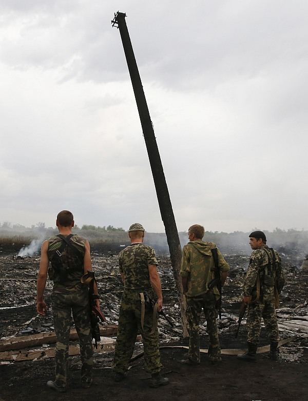 Armed pro-Russian separatists stnad at the site of a Malaysia Airlines Boeing 777 plane crash near the settlement of Grabovo in the Donetsk region,