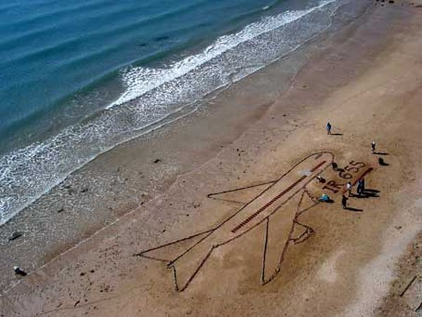 Remembering the tragedy, children draw a plane with IR 655 below it on the sand.