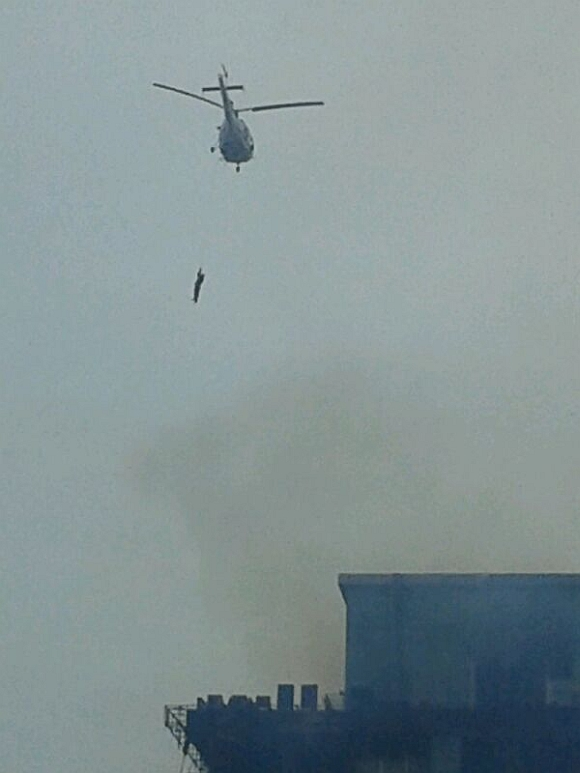 A chopper rescues firemen stranded in the building
