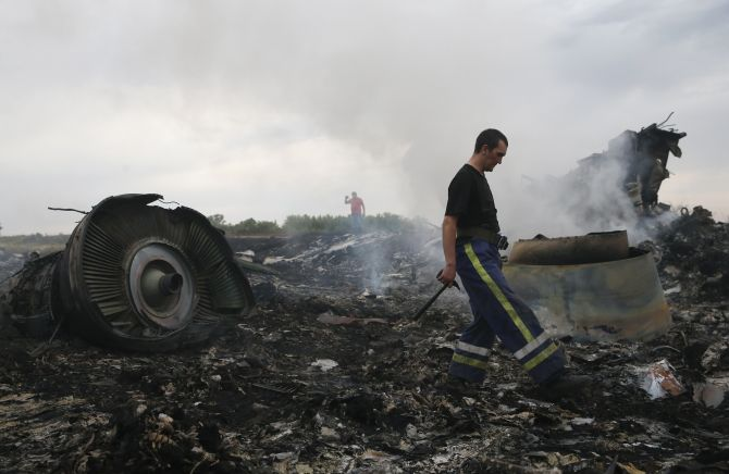 An Emergencies Ministry member (front) walks at the site of a Malaysia Airlines Boeing 777 plane crash near the settlement of Grabovo in the Donetsk region.