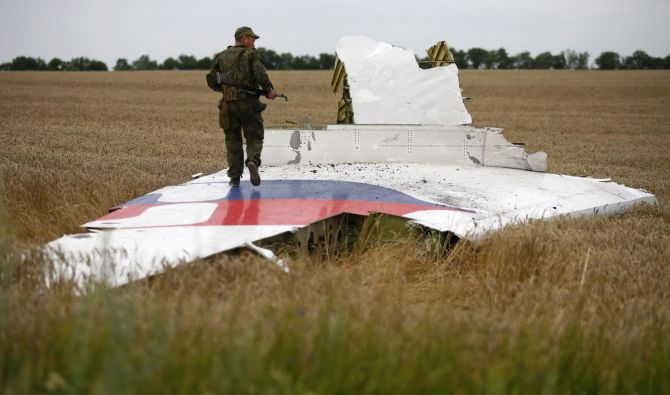 An armed pro-Russian separatist stands on part of the wreckage of the Malaysia Airlines Boeing 777 plane after it crashed near the settlement of Grabovo in the Donetsk region.