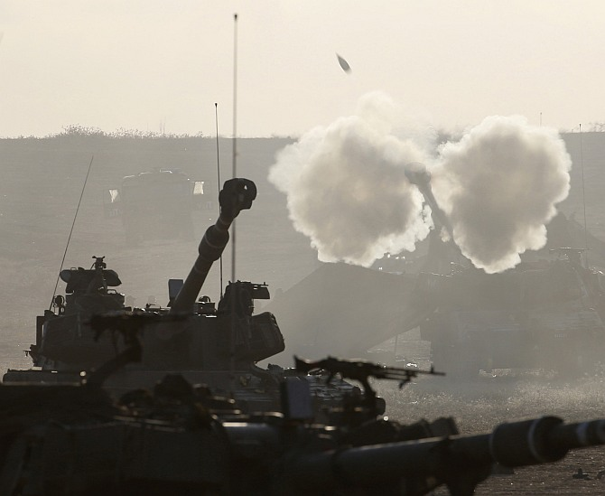 An Israeli mobile artillery unit fires towards Gaza from outside the northern Gaza Strip