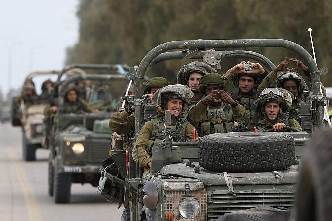 Israeli soldiers ride army jeeps near Sufa, outside the southern Gaza Strip