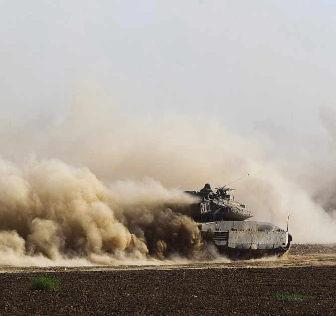 An Israeli soldier sits atop an armoured personnel carrier (APC) as it drives after the end of a five-hour humanitarian truce, near the border with the Gaza Strip