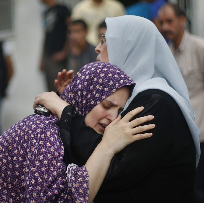The mother (C) of two boys from the Shaibar family, whom medics said were killed along with a girl from the same extended family by an Israeli air strike after the end of a five-hour humanitarian ceasefire, grieves during their funeral outside a hospital morgue in Gaza City