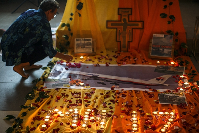 A woman lights candles at a memorial for victims of the downed Malaysia Airlines Flight MH17 in Kuala Lumpur