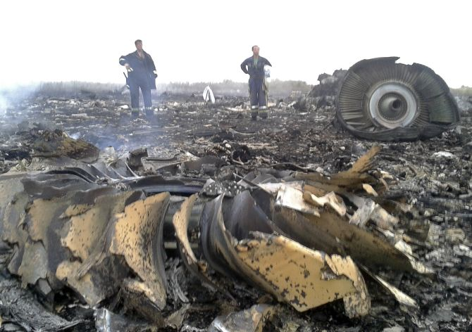 Officials overlook the debris of downed flight MH17 after it went down on Thursday evening.