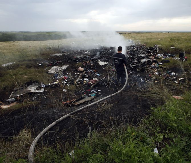 Officials pour water on the burning debris of Flight MH17