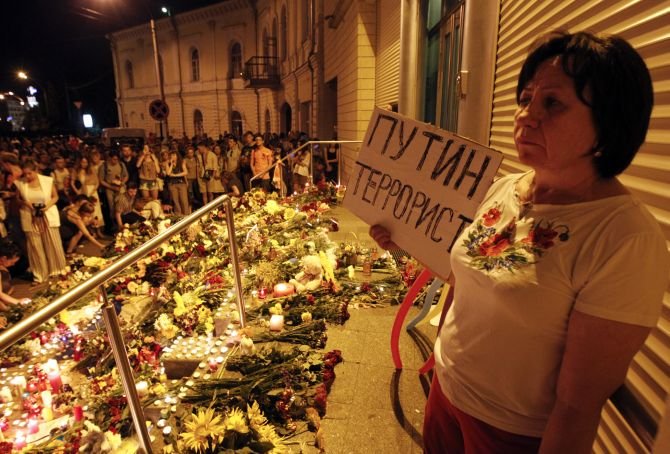 A woman stands with a placard that read 'Putin is a terrorist' at a memorial for the victims of flight MH17.