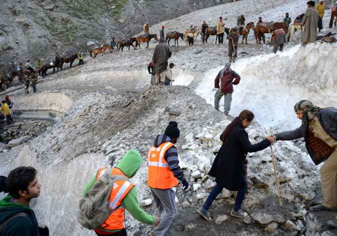 Security personnel assist the pilgrims proceeding towards the Holy Amarnath cave on Saturday