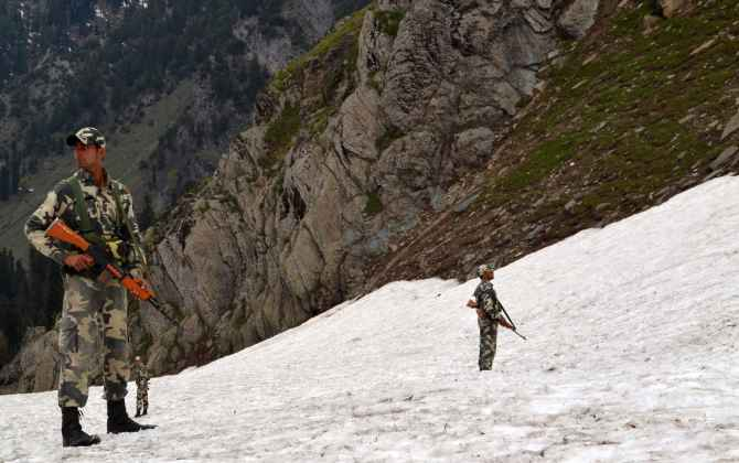 Security personnel guard the hills as pilgrims proceed to the Holy Amarnath cave from Baltel route on Saturday
