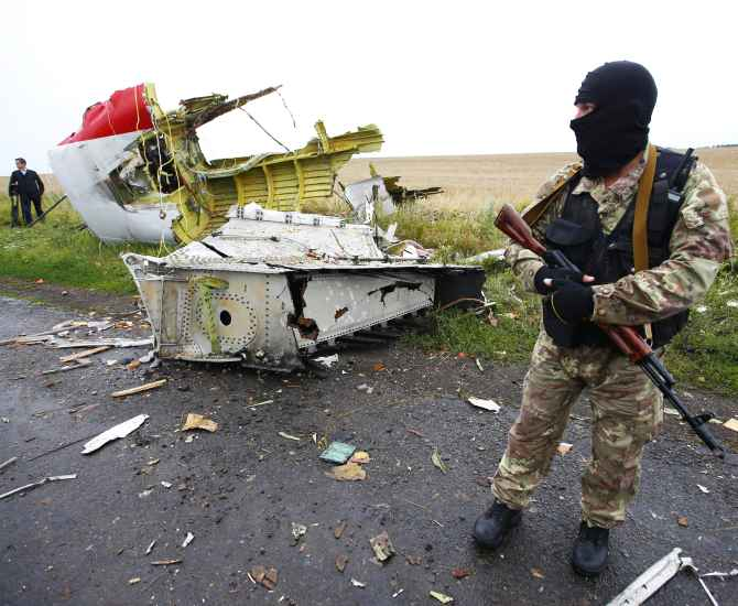 A pro-Russian separatist stands at the crash site of Malaysia Airlines flight MH17, near the settlement of Grabovo in the Donetsk region of Ukraine.