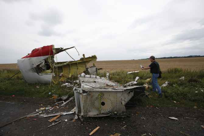An Organisation for Security and Cooperation in Europe monitor takes a photograph at the crash site of Malaysia Airlines flight MH17, near the settlement of Grabovo