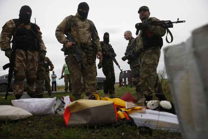 Pro-Russian separatists look at passengers' belongings at the crash site of Malaysia Airlines flight MH17 near the settlement of Grabovo