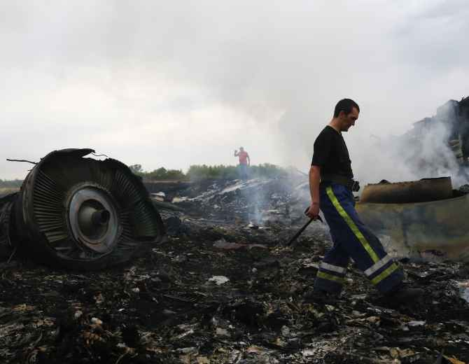 An Emergencies Ministry member walks at the site of a Malaysia Airlines Boeing 777 plane crash near the settlement of Grabovo