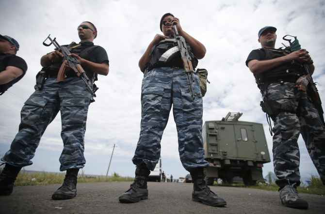 Armed pro-Russian separatists stand guard at a crash site of Malaysia Airlines Flight MH17