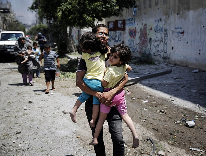 A Palestinian man carries children in the Shejaia neighbourhood, which was heavily shelled by Israel during fighting, in Gaza City