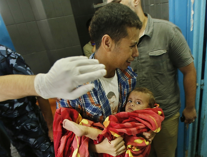 A Palestinian man reacts as he carries a boy, who medics said was wounded in Israeli shelling, at a hospital in Gaza City