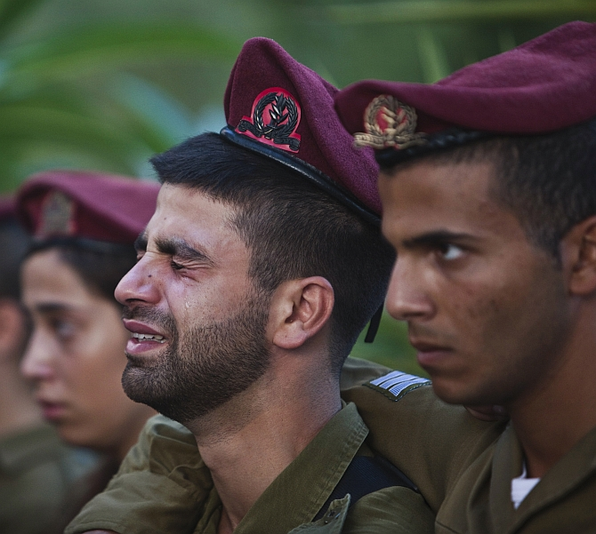 Israeli soldiers mourn during the funeral of their comrade Bnaya Rubel in Holon, near Tel Aviv