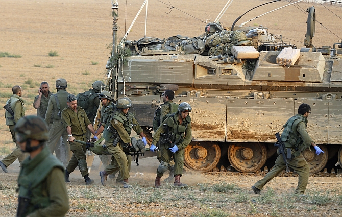 Israeli soldiers carry a comrade on a stretcher, who was wounded during an offensive in Gaza, outside northern Gaza