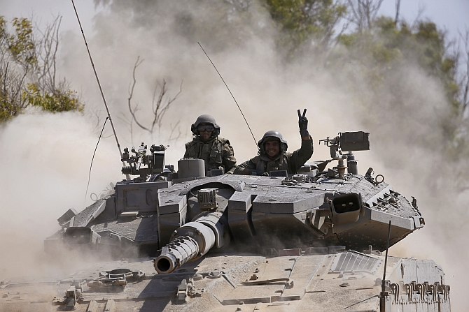 An Israeli soldier gestures from a tank near the border with Gaza