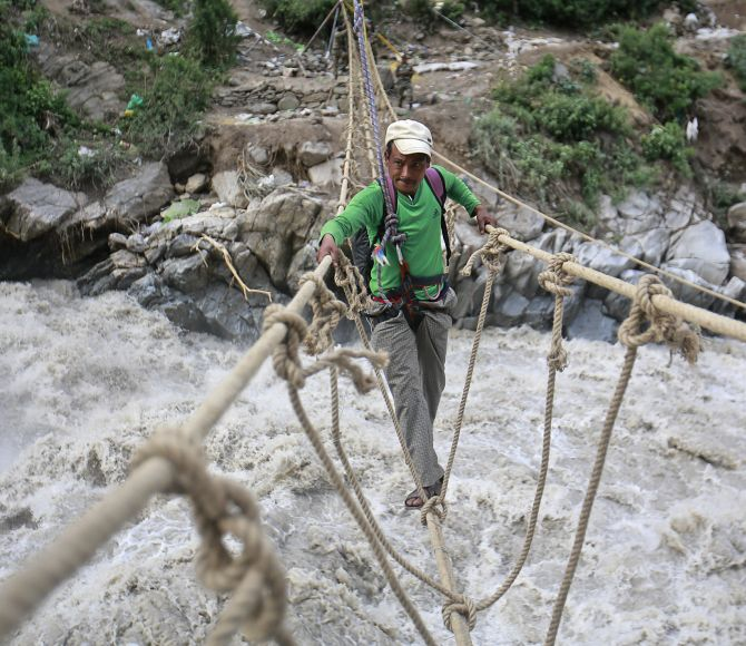 A man crosses a rope bridge over the Alaknanda river during rescue operations in Govindghat in the Himalayan state of Uttarakhand during the 2013 floods.