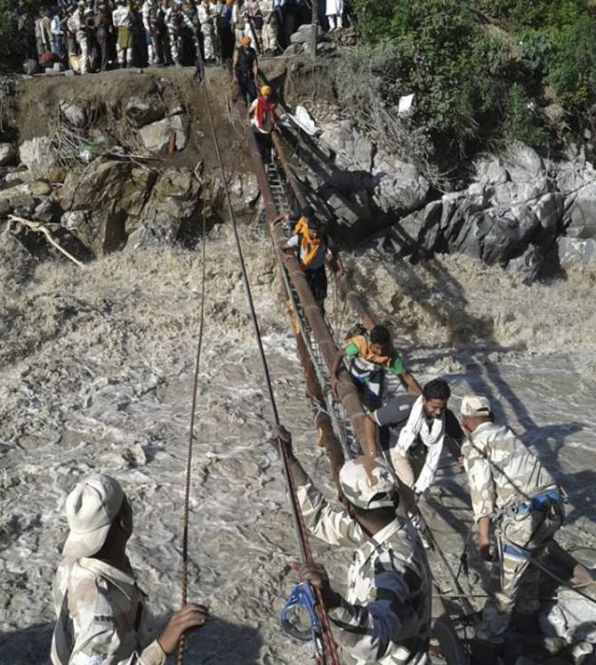 The Indo-Tibetan Border Police personnel rescue stranded people across a flooded river after heavy rains in Uttarakhand.
