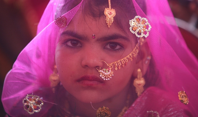 A veiled girl waits for her engagement in Gujarat
