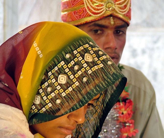 A young bride and groom sit in a temple during their marriage ceremony at a temple in Rajgarh district, Bhopal