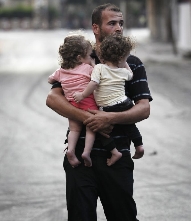 A Palestinian man carrying children flees the Shujayeh neighbourhood in a vehicle during heavy Israeli shelling in Gaza.