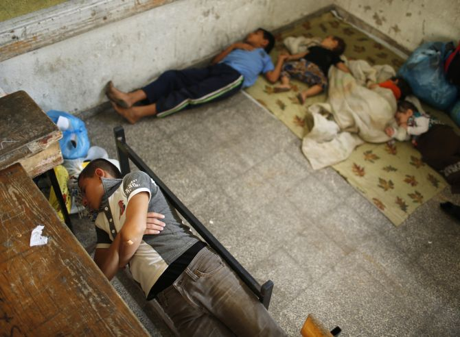 Palestinian children, who fled their family house that is adjacent to the border with Israel, sleep as they stay at a United Nations-run school in Gaza city.