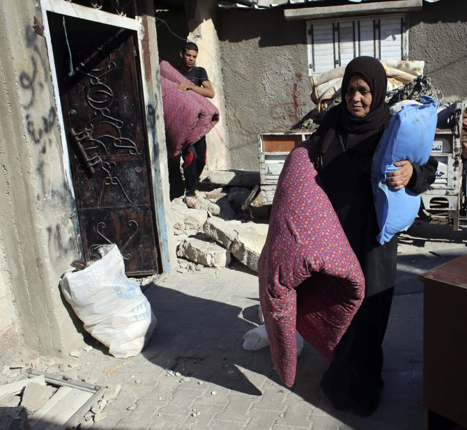 A Palestinian woman carries belongings as she flees her house, in Rafah in the southern Gaza Strip