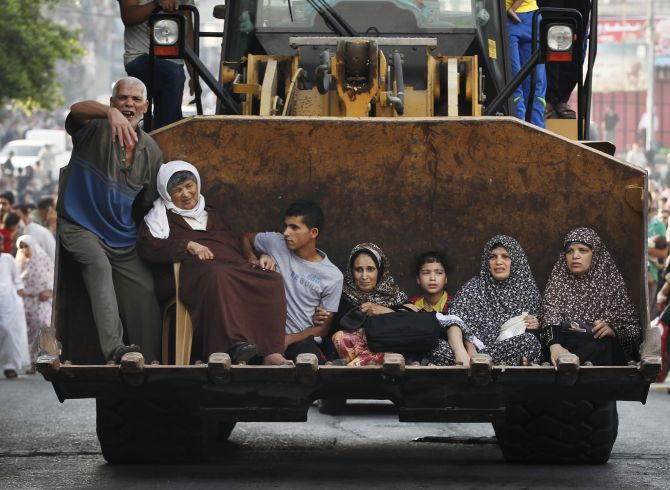 Palestinians sit in the bucket of an excavator as families flee the Shujayeh neighbourhood during heavy Israeli shelling in Gaza city.