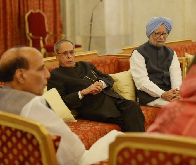 President Pranab Mukherjee speaks to Union Home Minister Rajnath Singh as former Prime Minister Manmohan Singh looks on