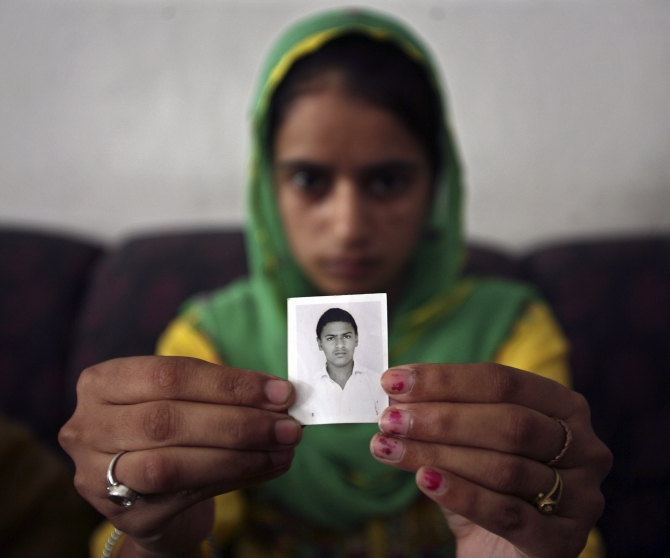 Paramjit Kaur displays the photograph of her brother Kuljit Singh, who has been kidnapped in Iraq, in Amritsar.