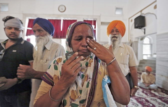 A relative of an Indian worker, who has been kidnapped in Iraq, weeps during her visit to a Gurudwara before meeting Swaraj in New Delhi.