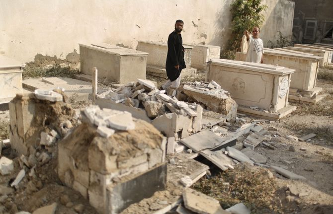 Palestinians inspect a cemetery which police said was damaged in Israeli shelling, in Gaza City
