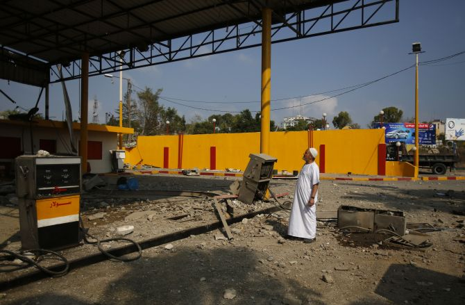 A Palestinian man looks at a petrol station which police said was damaged in an Israeli air strike, in Gaza City