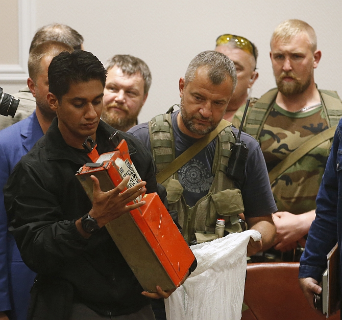 Malaysian expert examines a black box belonging to Malaysia Airlines flight MH17 during its handover from pro-Russian separatists, in Donetsk