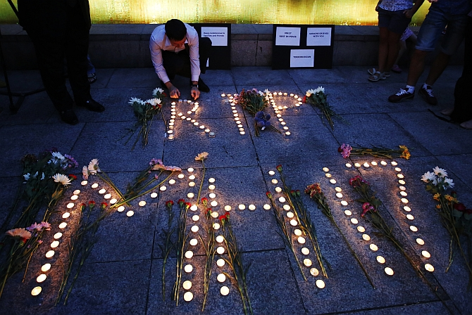 A man from the Ukrainian community living in Malaysia lights candles for a memorial to the victims of Malaysia Airlines Flight MH17, which was downed over eastern Ukraine, in Kuala Lumpur